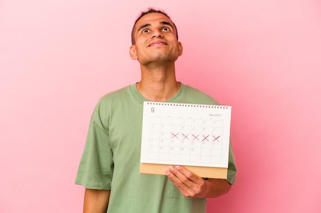 Jeune homme vénézuélien tenant un calendrier isolé sur fond rose rêvant d'atteindre ses objectifs