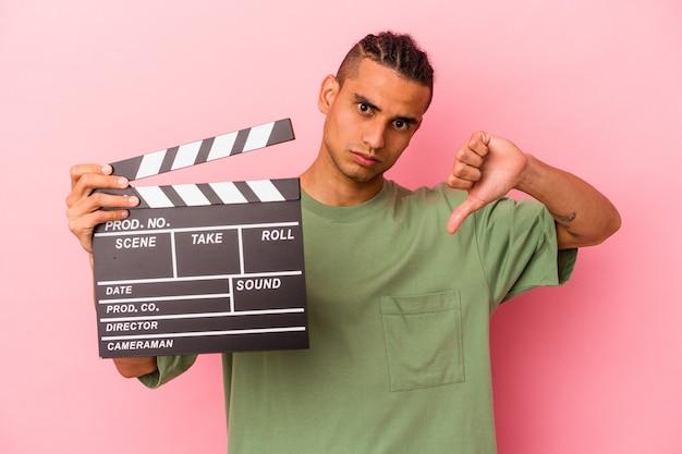 Jeune homme vénézuélien tenant un clap isolé sur fond rose montrant un geste d'aversion, les pouces vers le bas. notion de désaccord.