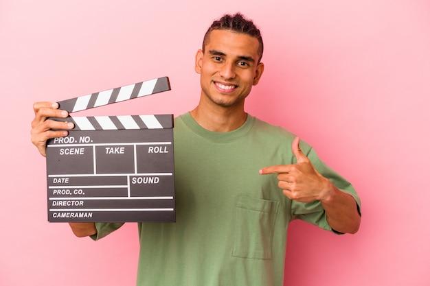 Jeune homme vénézuélien tenant un clap isolé sur fond rose personne pointant à la main vers un espace de copie de chemise, fier et confiant