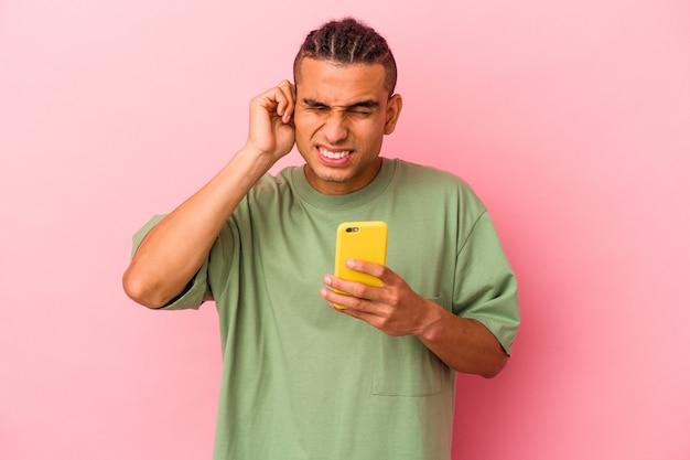 Jeune homme vénézuélien tenant un téléphone portable isolé sur fond rose couvrant les oreilles avec les mains.