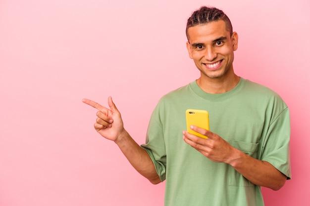 Jeune homme vénézuélien tenant un téléphone portable isolé sur fond rose souriant et pointant de côté, montrant quelque chose dans un espace vide.