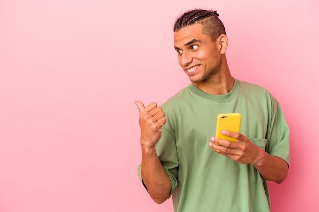 Jeune homme vénézuélien tenant un téléphone portable isolé sur des points de fond rose avec le pouce loin, riant et insouciant.