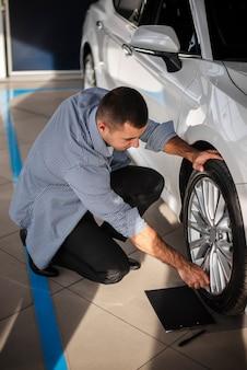 Jeune homme vérifiant une voiture chez un concessionnaire