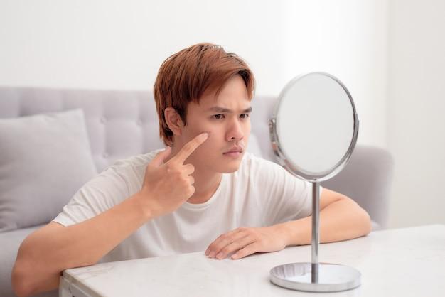 Le jeune homme vérifie dans le miroir de votre peau de problème