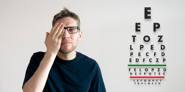 Jeune homme vérifier la vision de la vue, examiner la santé avec le tableau des lettres de test