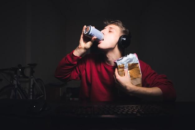Jeune homme avec un verre et une collation à la main, assis devant l'ordinateur