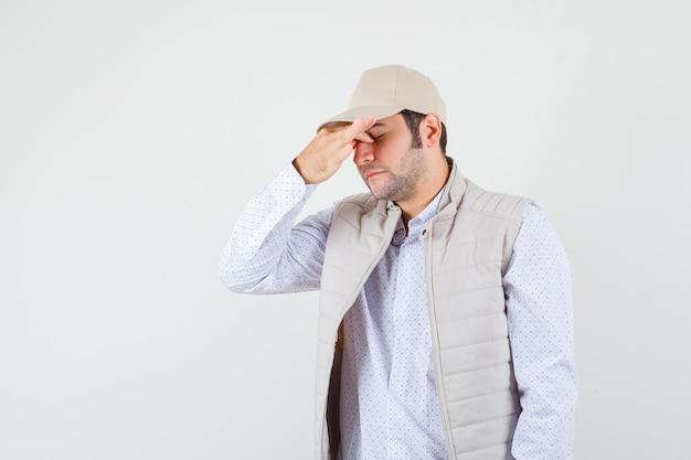 Jeune homme en veste beige et casquette couvrant une partie du visage avec la main et l'air fatigué, vue de face.