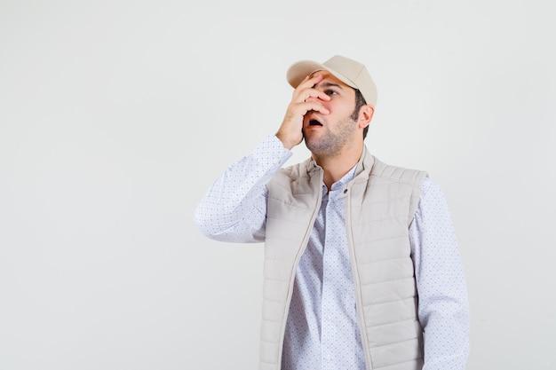 Jeune homme en veste beige et casquette couvrant une partie du visage avec la main et à la surprise, vue de face.