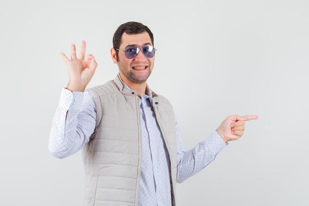 Jeune homme en veste beige et casquette mettant des lunettes tout en pointant vers la droite avec l'index et montrant le signe ok et à l'optimiste, vue de face.