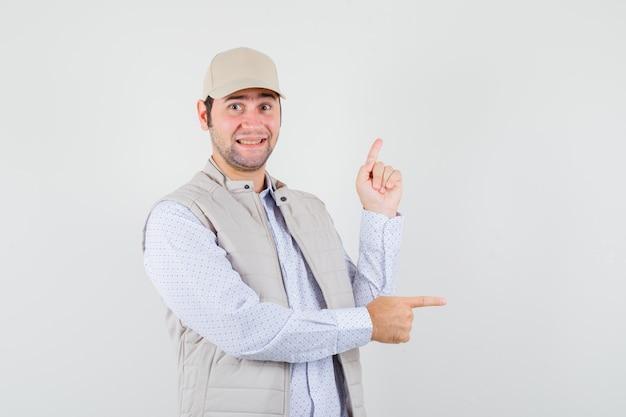 Jeune homme en veste beige et casquette pointant vers la droite avec l'index et à la vue de face, heureux.