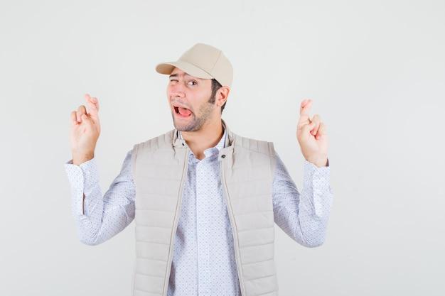 Jeune homme en veste beige et casquette tenant les doigts croisés et collant la langue et à la vue de face, heureux.