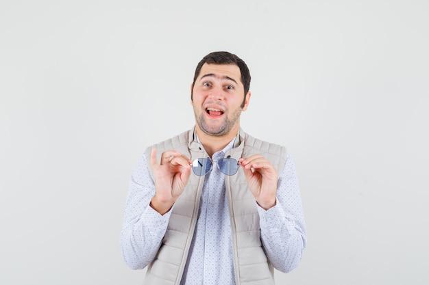 Jeune homme en veste beige et casquette tenant des lunettes à deux mains et à l'optimiste, vue de face.