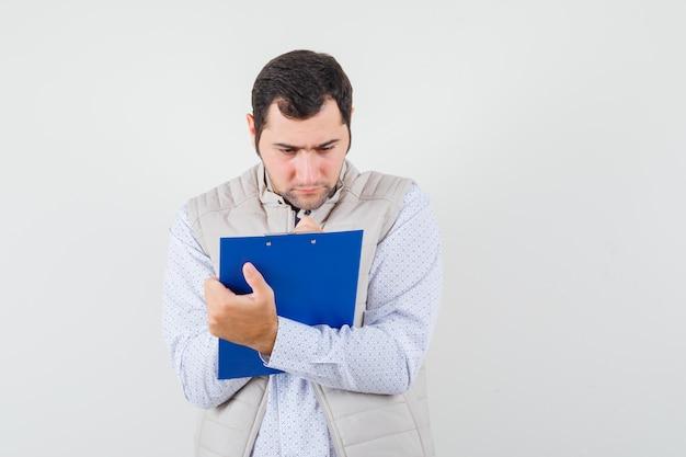 Jeune homme en veste beige écrit quelque chose sur le cahier avec un stylo et à la vue de face, focalisée.