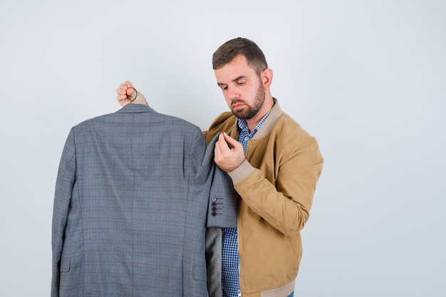 Jeune homme en veste, chemise regardant des costumes, debout sur le côté et à la perplexité.