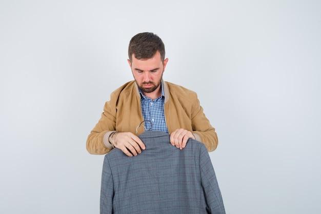Jeune homme en veste, chemise tenant un costume devant lui et regardant perplexe, vue de face.
