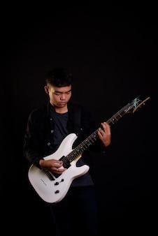 Jeune homme en veste de cuir noir avec guitare électrique