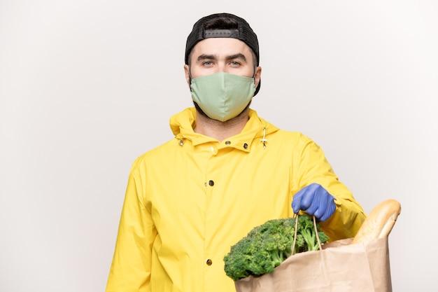 Jeune homme en veste jaune et bonnet noir avec respirateur sur le visage et des gants sur les mains transportant un sac en papier avec des légumes frais du supermarché