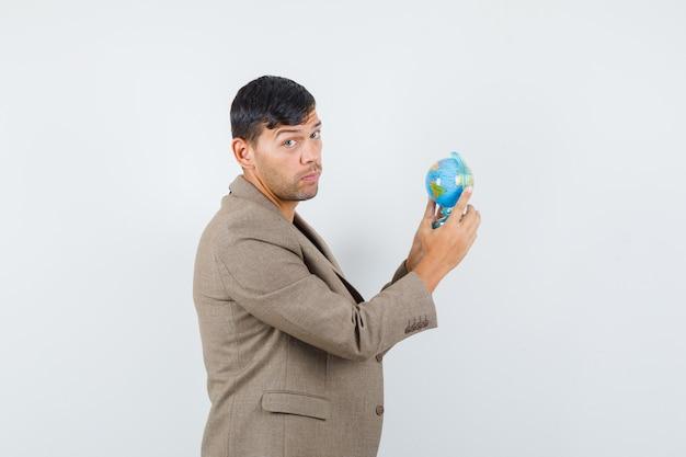 Jeune homme en veste marron grisâtre, chemise noire regardant de côté tout en tenant un mini globe et à la confusion, vue de face.