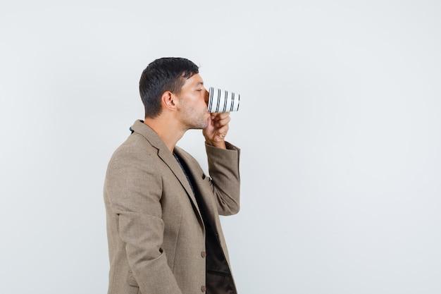 Jeune homme en veste marron grisâtre de l'eau potable et à la soif