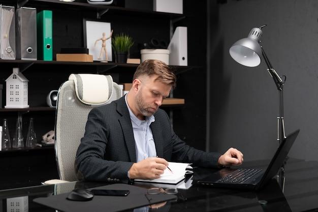Jeune homme en vêtements d'affaires travaillant avec un ordinateur portable et un journal