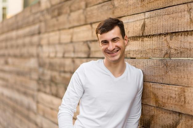 Un jeune homme en vêtements blancs posant près d'un mur en bois