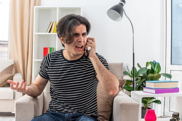 Jeune Homme En Vêtements Décontractés Ayant L'air Confus Et Mécontent Tout En Parlant Au Téléphone Portable Assis Sur La Chaise Dans Un Salon Lumineux Photo gratuit