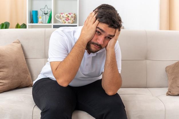 Jeune homme en vêtements décontractés ayant l'air déprimé avec les mains sur la tête, assis sur un canapé dans un salon lumineux