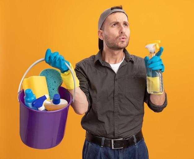 Jeune homme en vêtements décontractés et cap holding seau avec des outils de nettoyage à côté perplexe debout sur le mur orange