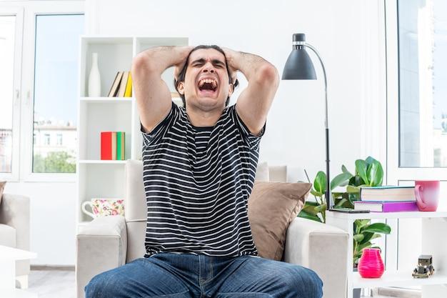 Jeune homme en vêtements décontractés criant d'être frustré par les mains sur la tête, assis sur la chaise dans un salon lumineux