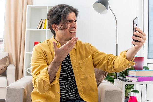 Jeune homme en vêtements décontractés faisant du selfie à l'aide d'un smartphone, l'air en colère et frustré assis sur la chaise dans un salon lumineux