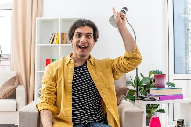 Jeune homme en vêtements décontractés heureux et surpris montrant l'index ayant une nouvelle idée géniale assis sur la chaise dans un salon lumineux