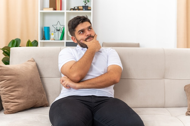 Jeune homme en vêtements décontractés levant perplexe avec la main sur le menton assis sur un canapé dans un salon lumineux