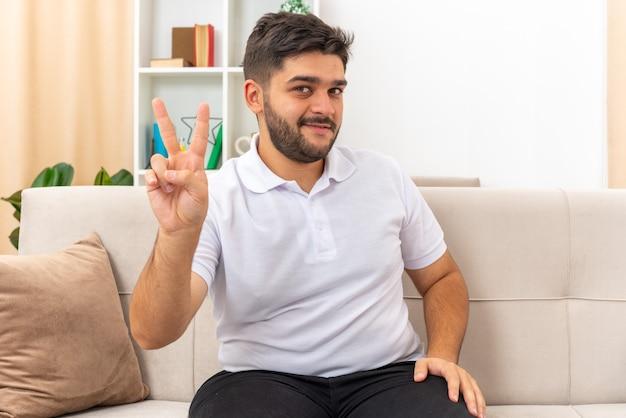 Jeune homme en vêtements décontractés à la recherche de sourire gaiement montrant v-sign assis sur un canapé dans un salon lumineux