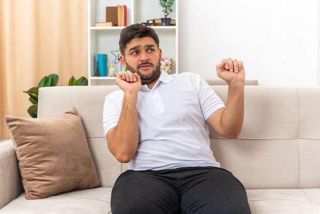 Jeune homme en vêtements décontractés regardant de côté inquiet en faisant un geste de défense assis sur un canapé dans un salon lumineux