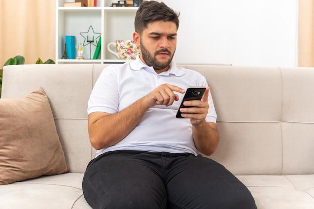 Jeune homme en vêtements décontractés tenant un smartphone en train de taper divers messages en regardant l'écran avec un visage sérieux assis sur un canapé dans un salon lumineux