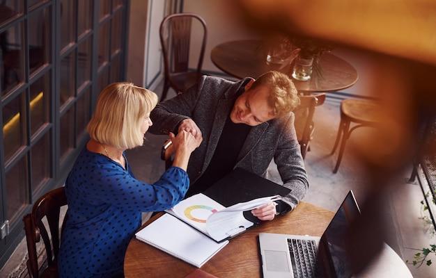 Un jeune homme en vêtements formels a une discussion d'affaires avec une vieille femme au café.
