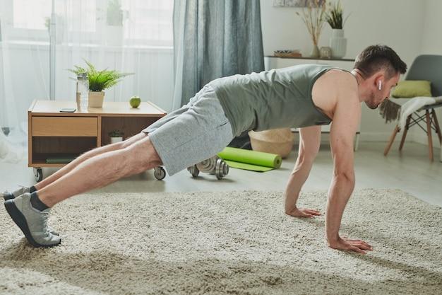 Jeune homme en vêtements de sport et écouteurs faisant des pompes sur le sol du salon à la maison pendant la période de quarantaine
