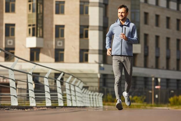 Jeune homme en vêtements de sport jogging le long de la rue de la ville