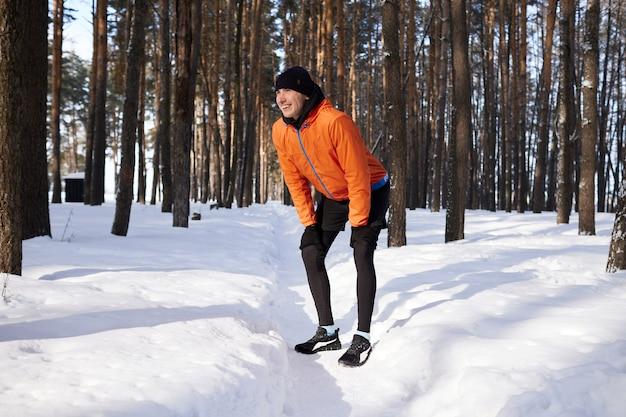 Un jeune homme en vêtements de sport lumineux aime courir à travers la forêt un jour d'hiver
