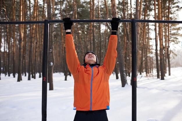 Un jeune homme en vêtements de sport lumineux est engagé dans une séance d'entraînement sur un terrain de sport un jour d'hiver
