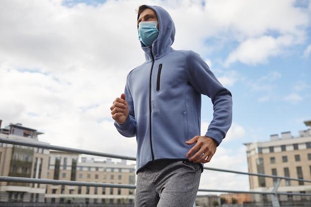 Jeune homme en vêtements de sport et en masque de protection jogging dans la ville en plein air