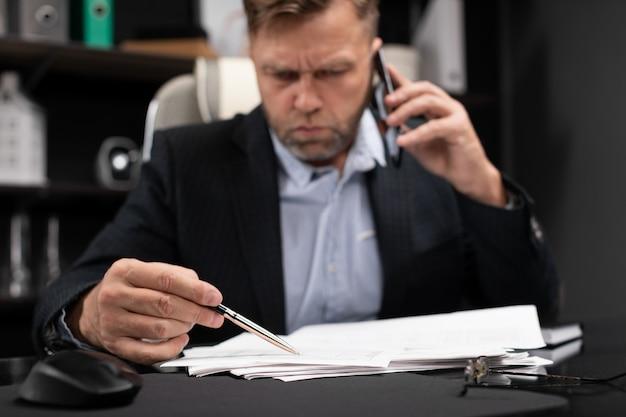 Jeune homme en vêtements de travail travaillant à l'ordinateur de bureau avec téléphone et documents