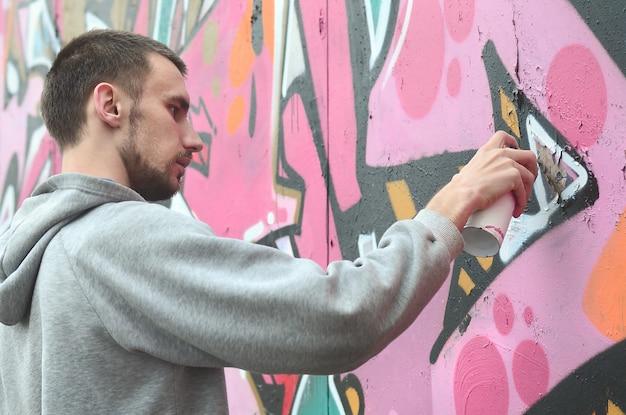 Un jeune homme vêtu d'une capuche grise peint des graffitis de couleur rose et verte