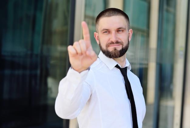 Un jeune homme vêtu d'une chemise blanche et d'une cravate appuie son index sur l'écran virtuel de l'écran tactile