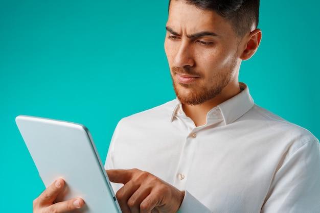 Jeune homme vêtu d'une chemise blanche tient une tablette numérique sur fond vert