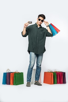 Un jeune homme vêtu d'une chemise sombre et d'un jean, portait plusieurs sacs pour faire du shopping avec une carte de crédit