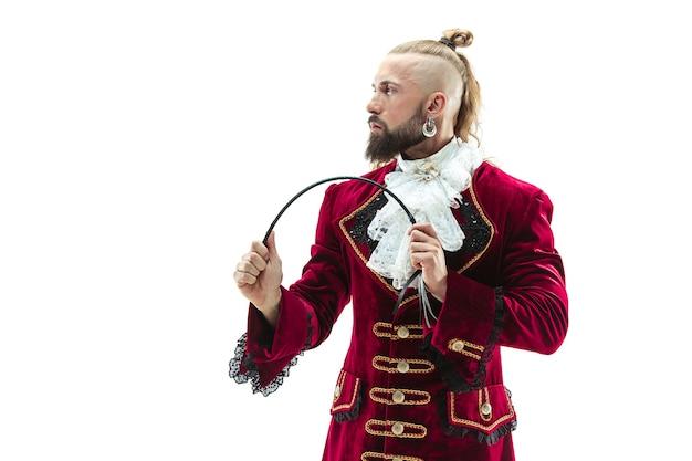 Le jeune homme vêtu d'un costume médiéval traditionnel de marquis posant au studio avec fouet.