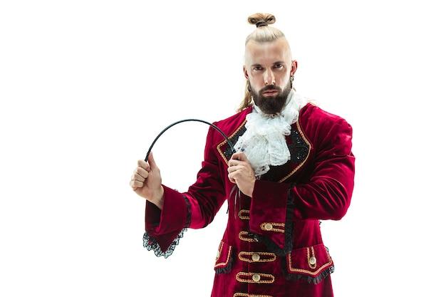 Le jeune homme vêtu d'un costume médiéval traditionnel de marquis posant au studio avec fouet