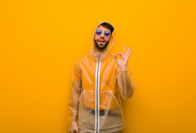 Jeune homme vêtu d'un manteau de pluie gai et confiant faisant geste ok