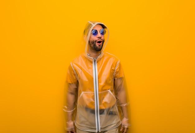 Jeune homme vêtu d'un manteau de pluie rêvant d'atteindre ses objectifs